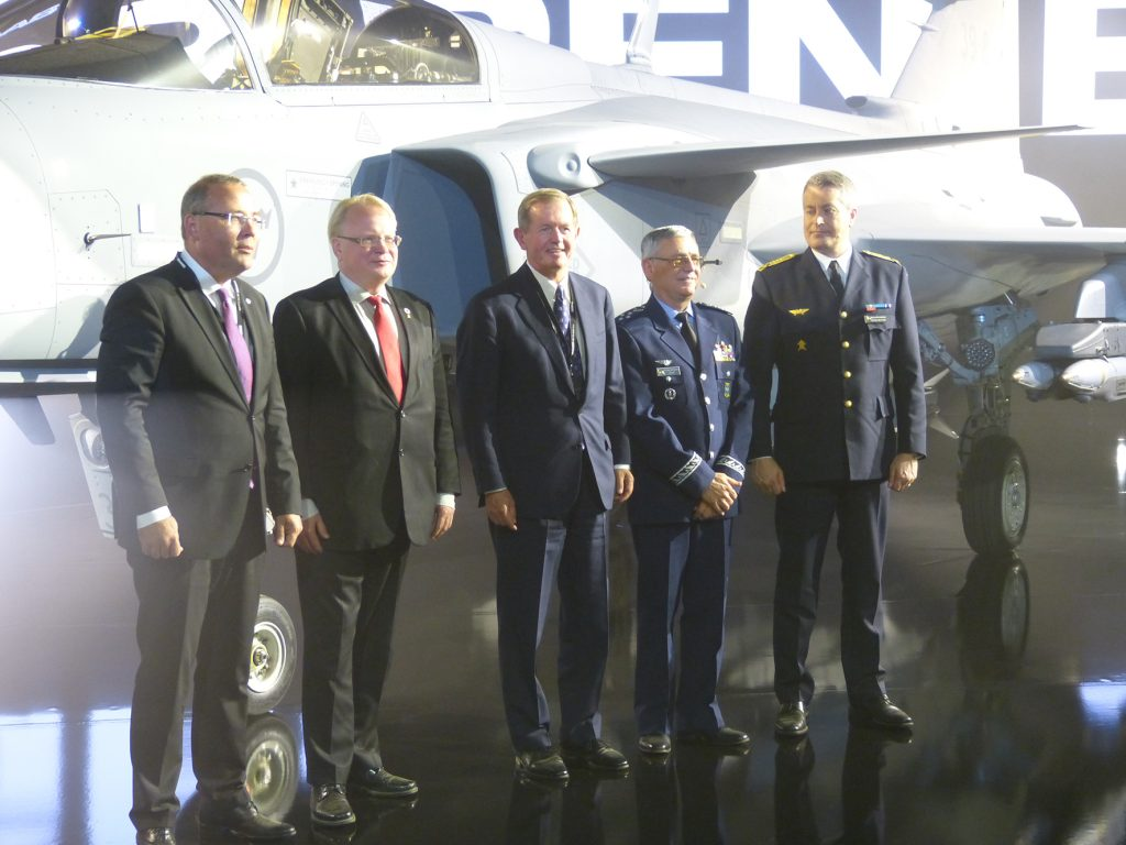 VIPs attending the Gripen E unveiling, left to right, Saab CEO Håkan Buskhe, Sweden's Minister of Defence Peter Hultqvist, Head of Saab Aeronautics Ulf Nilsson, Chief of the Brazilian Air Force Tenente Brigadier General Nivaldo Luiz Rossato, and the Chief of the Swedish Air Force General Mats Helgesson. (David Oliver)