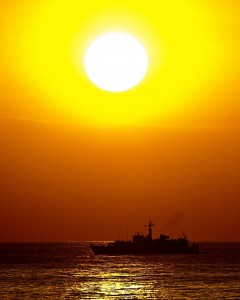 The Royal Navy's Sandown Class Minehunter HMS Pembroke is pictured with the sun setting behind her as she enters Dubai during operations in the Middle East.