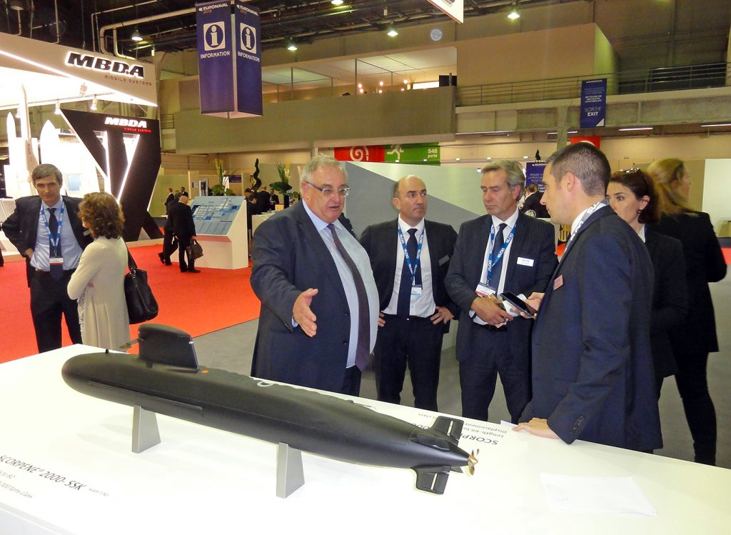 Hervé Guillou, CEO of DCNS (at left), in conversation with members of his personnel in front of a 1/50 scale model of the 5,000-ton Scorpene 2000; the latest export variant of this very successful SSK. © J.-M. Guhl